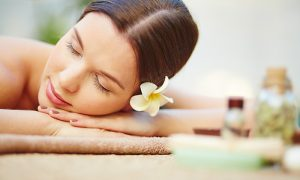 Relaxed female with frangipani flower in hair lying in spa salon